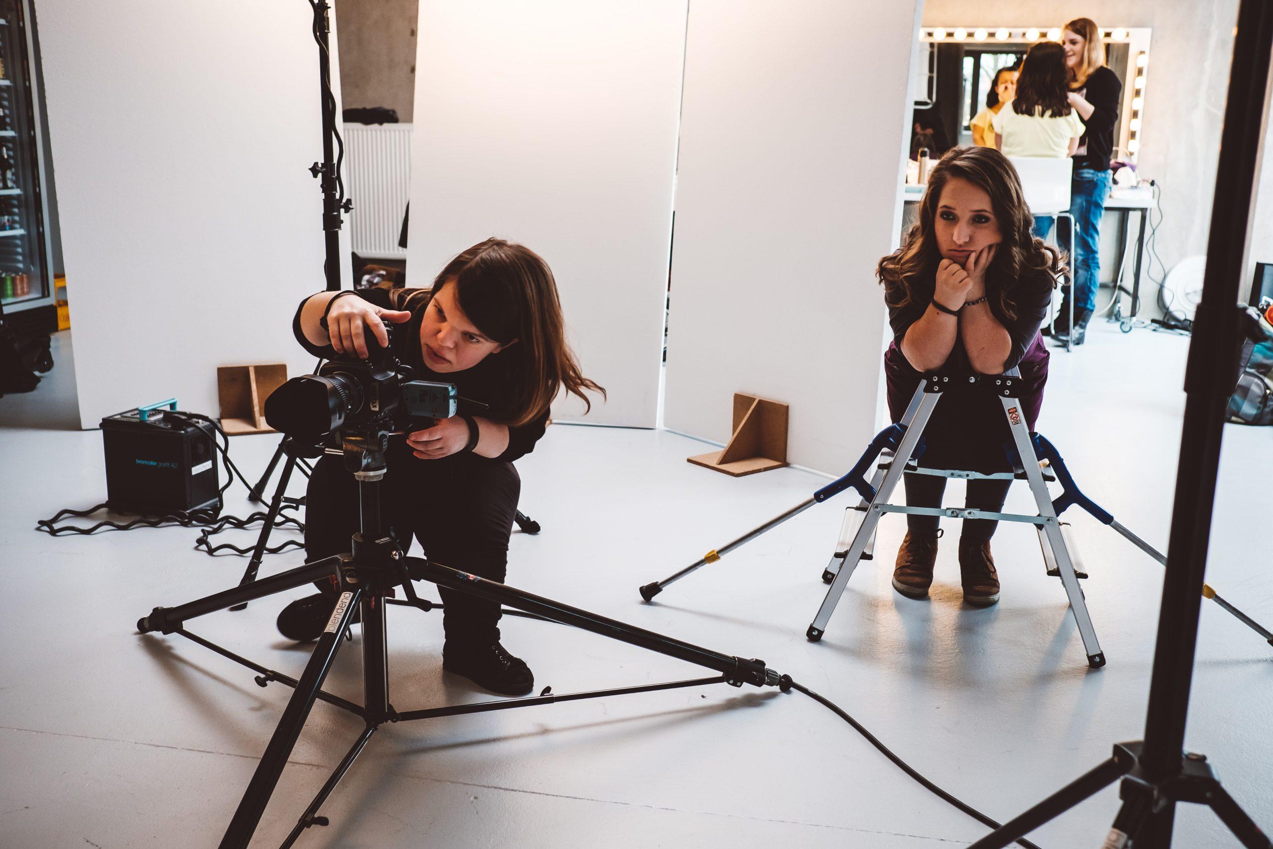 Fotografin mit Behinderung richtet ein Bild im Fotostudio ein. SIe steht hinter der Kamera und dem Stativ. Ihre Assistintin schaut ihr zu.