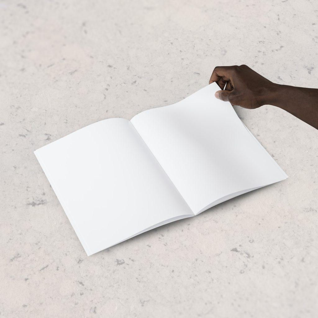 Ein aufgeschlagenes Schreibheft ohne jegliche Beschriftung. Ein Schwarzer Arm ist zu sehen mit einem Stift in der Hand, der die Seite an der rechten oberen Seite berührt.