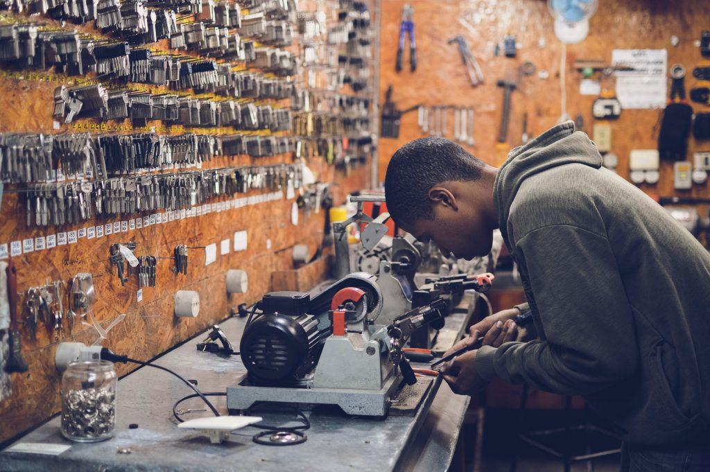 Ein Schwarzer junger Schlüsselmacher arbeitet an einer Schlüsselmaschine in seiner Werkstatt