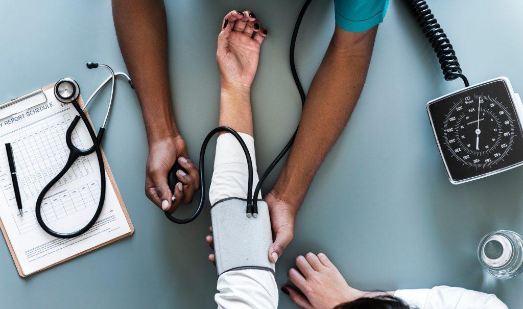 Ein Schwarzer Arzt, der an einem weißen Patienten den Blutdruck misst.