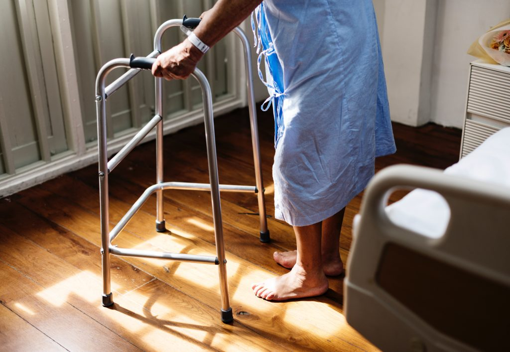 Ein älterer Mensch neben einem Krankenhausbett an einem Gehgestell sich aufstützend.