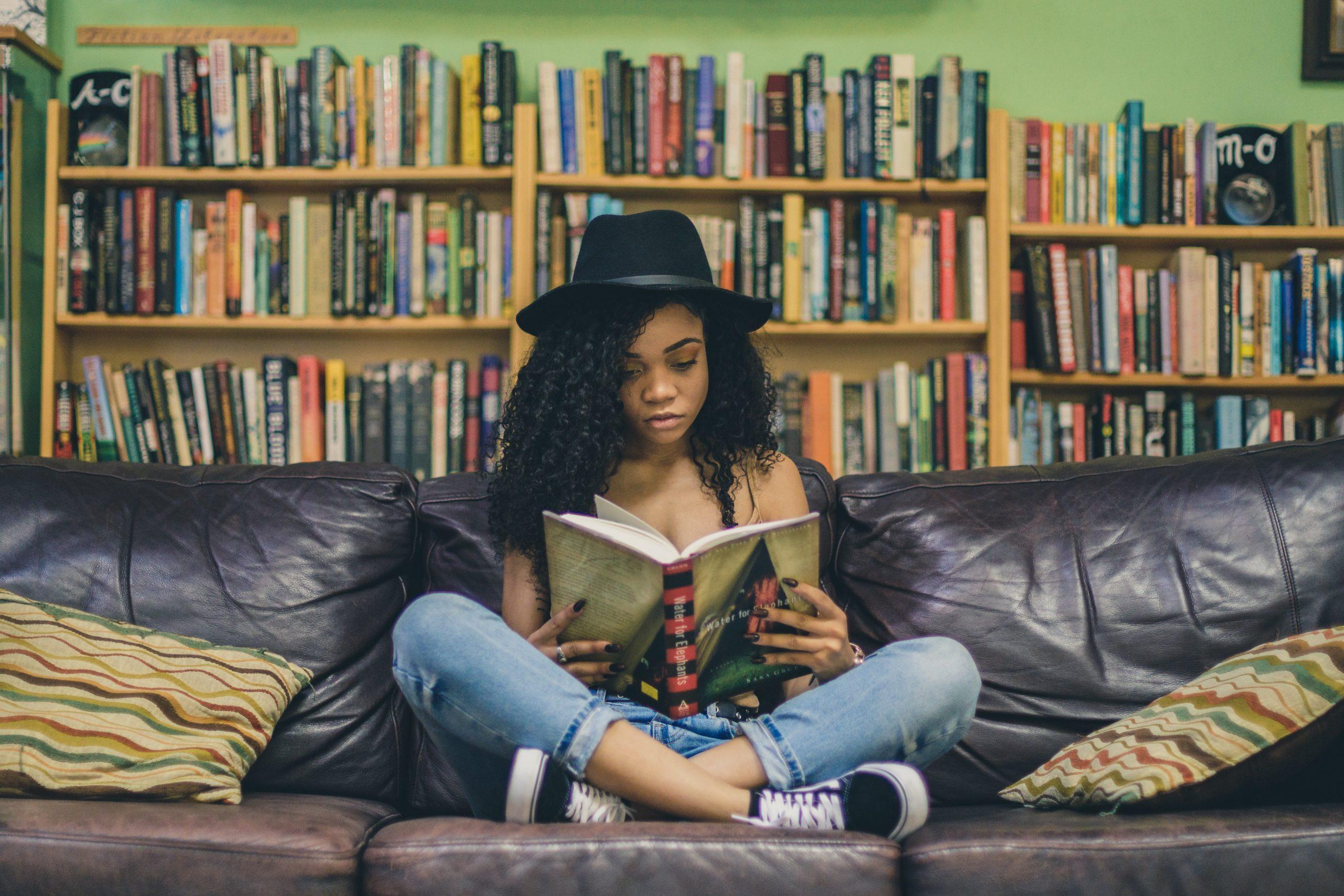 Eine Schwarze junge Frau, die im Schneidersitz auf einem Sofa vor einem riesen Bücherregal sitzt. Sie ist vertieft in ein Buch, was sie in ihren beiden Händen aufgeschlagen hat.