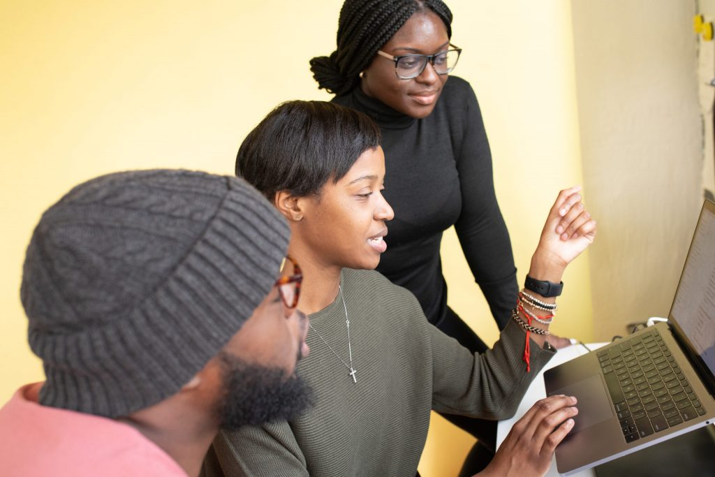 Drei Schwarze junge Menschen, die zusammen auf einen Laptop schauen und sich darüber unterhalten.