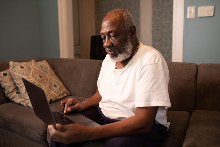 Ein Schwarzer älterer Herr, der auf dem Sofa mit seinem Laptop auf dem Schoss sitzt.