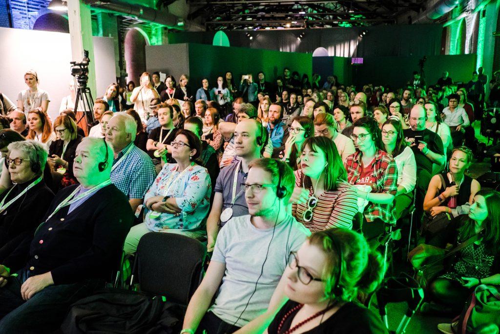 Eine Aufnahme des Publikums während einer Veranstaltung. Die Zuhörer:innen sitzen, einige tragen Kopfhörer. Ein grünes Licht fällt auf die die ca. 150 Zuschauenden.