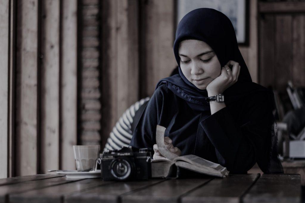Frau mit Hijab liest in einem Cafe.