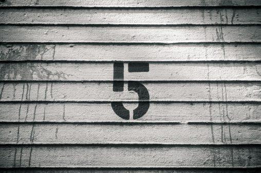 Die Zahl 5 an eine Holzwand angebracht